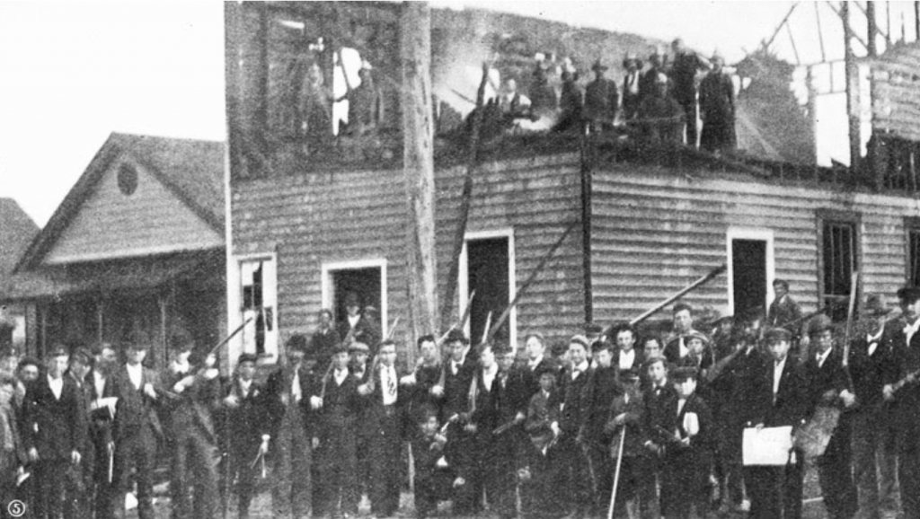Men gather outside the charred remains of The Daily Record after the 1898 massacre.LIBRARY OF CONGRESS